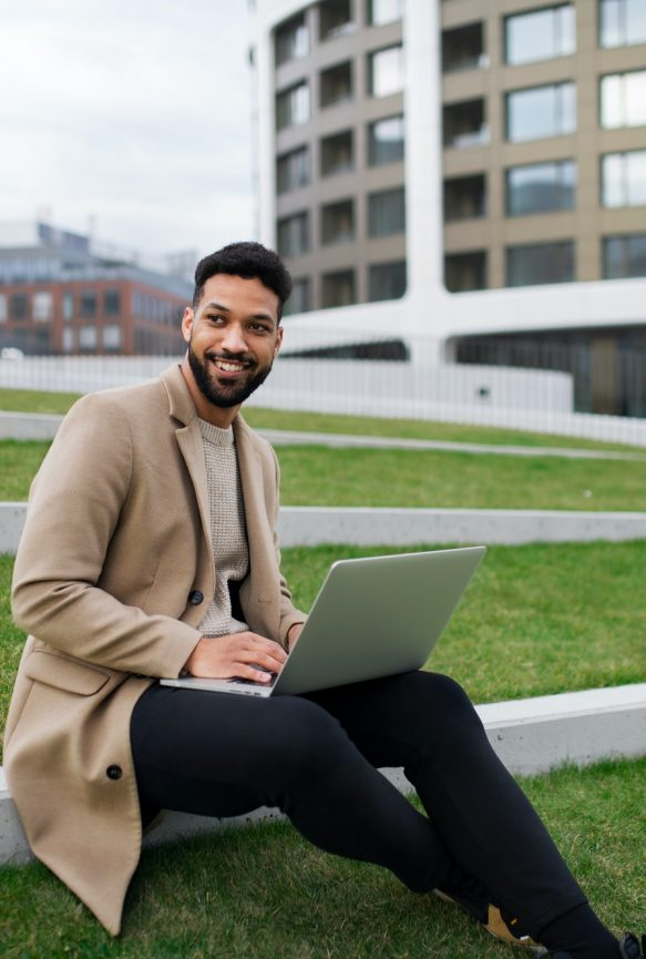 Man with laptop working outdoors in park in city, remote office concept